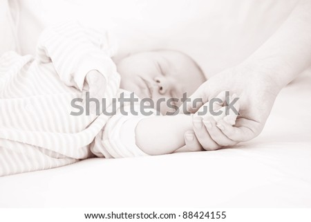 Mum holds by the hand the sleeping baby.