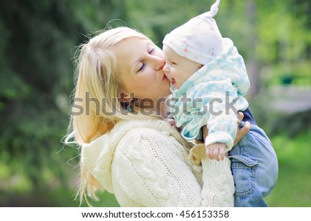 Mum kisses the small daughter on the cheek a walk in the Park, cool weather, close-up. - stock photo