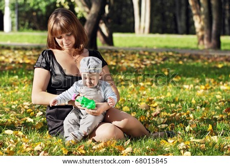 Mum plays with the one-year-old child a lawn in park - stock photo