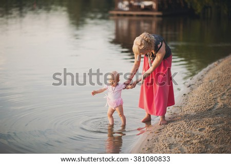 Mum plays with the small daughter near water, childhood, love, life style