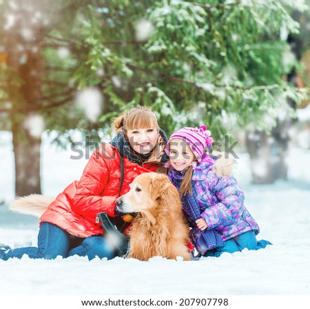 mum with a daughter and their dog in winter park - stock photo