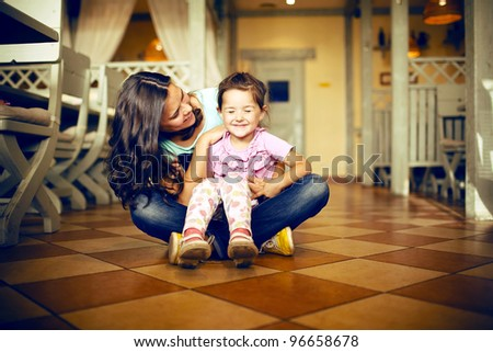 Mum with a daughter sit on a floor! - stock photo