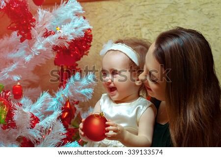 Mum with a little daughter decorate a Christmas tree and having fun. Christmas mood. New year. - stock photo