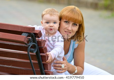 Mum with baby on a bench in the park, Beautiful Mother And Baby outdoors. Nature. Outdoor Portrait of happy family. Joy. Mom and Baby  - stock photo