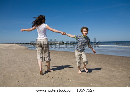 Mum with son playing on the beach