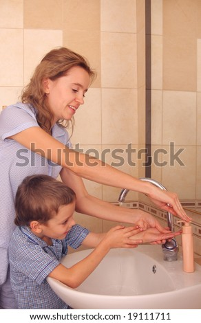 Mum with the son wash hands - stock photo