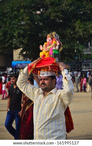 Mumbai, India - circa September 2013 - Man carrying Hindu god (Ganesha) over his head to immerse the Ganesha into the sea