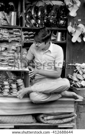 MUMBAI, INDIA - FEBRUARY 15, 1984: guy selling shoes in the biggest open air city market. The place is everyday populated by thousands of people.