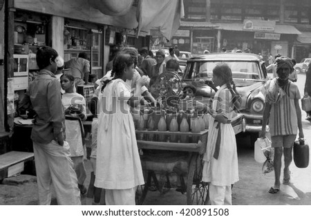 MUMBAI, INDIA - FEBRUARY 15, 1984: ladies drinking juice in the biggest open air city market. The place is everyday populated by thousands of people. - stock photo