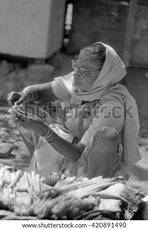 MUMBAI, INDIA - FEBRUARY 15, 1984: lady repairing and selling towels in the biggest open air city market. The place is everyday populated by thousands of people. - stock photo