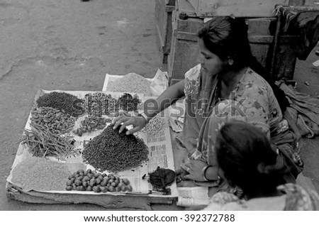 MUMBAI, INDIA - FEBRUARY 15, 1984: lady selling herbs, species and seeds at the biggest open air city market. The place is everyday populated by thousands of people. - stock photo