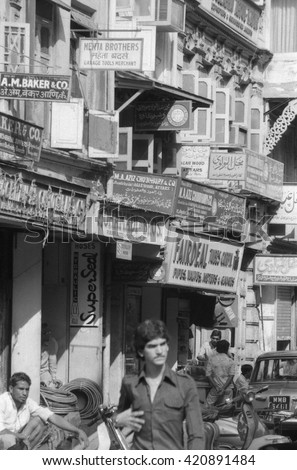 MUMBAI, INDIA - FEBRUARY 15, 1984: old houses and city life in one of the city main street. The place is every day extremely crowded. - stock photo
