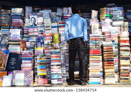 MUMBAI, INDIA - FEBRUARY 13: Piles of books on the booksellers-street on Febuary 13, 2012 in Mumbai. Here can buy books, originals and counterfeits, at 20-60% of the listed publisher's price;   - stock photo