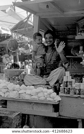MUMBAI, INDIA - FEBRUARY 15, 1984: salt vendor with his child at  the biggest open air city market. The place is everyday populated by thousands of people.