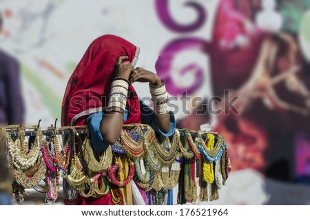Mumbai, India - February 8, 2014 - Woman in traditional Indian saree dresses selling ornamental necklaces along the busy street of South Mumbai  - stock photo