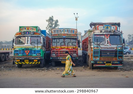 MUMBAI, INDIA - 05 FEBRUARY 2015: Woman walking by parked trucks on highway rest area decorated in traditional Indian style.