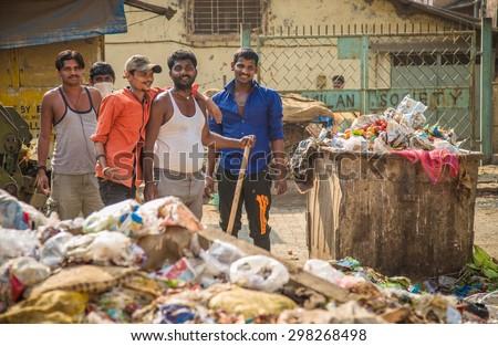 MUMBAI, INDIA - 16 JANUARY 2015: Five adult garbage men pile up garbage on slum street before throwing into garbage truck. - stock photo