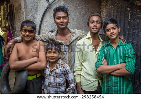 MUMBAI, INDIA - 12 JANUARY 2015: Five Indian boys from Dharavi slum stand in street. Dharavi is one of the largest slums in the world. - stock photo