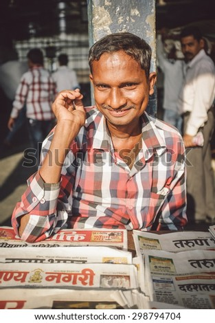 MUMBAI, INDIA - 08 JANUARY 2015: India man sells newspapers in front of train station. Post-processed with grain, texture and colour effect. - stock photo