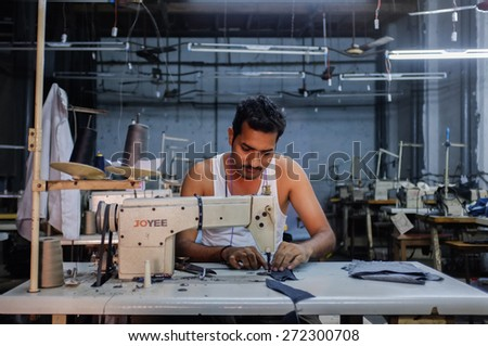 MUMBAI, INDIA - 12 JANUARY 2015: Indian worker sowing in a clothing factory in Dharavi slum - stock photo