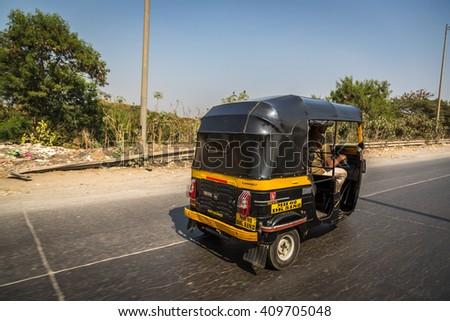 Mumbai, India - January 10th 2016 - One black rickshaw driving through Mumbai's street, India. - stock photo
