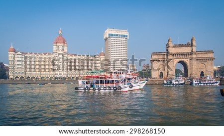 MUMBAI, INDIA - 17 JANUARY 2015: The Gateway of India is a monument built during the British Raj in Mumbai. Taj Mahal Palace Hotel is a five-star hotel located in the Colaba region of Mumbai. - stock photo