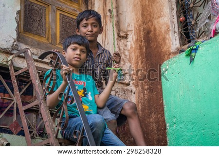 MUMBAI, INDIA - 12 JANUARY 2015: Two young boys sit on high stairs in front of home in Dharavi slum. Dharavi is one of the largest slums in the world. - stock photo