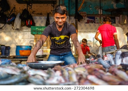 MUMBAI, INDIA - 08 JANUARY 2015: Worker at a fishmarket posing while waiting for customers. - stock photo
