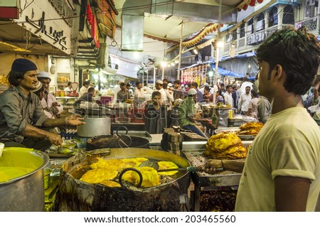 Mumbai, India - July 3, 2014 - Men frying snack in hot oil pan from stall at at crowded Mohammad Ali Road in the evening during Ramzan fasting month - stock photo