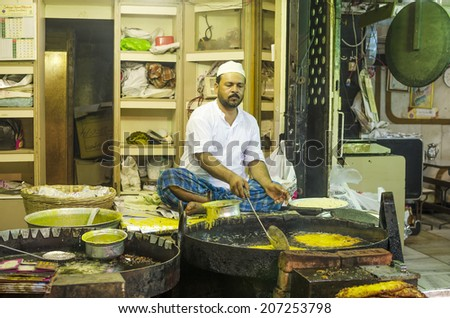 Mumbai, India - July 3, 2014 -  Muslim man frying snack in hot oil pan from stall at crowded Mohammad Ali Road in the evening during Ramzan fasting month - stock photo