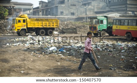 MUMBAI, INDIA - NOV 13: Unidentified child is playing cricket next to a garbage disposal area in a slum on November 13, 2012 in Mumbai, India. Over 60% of population lives in slums in Mumbai.  - stock photo