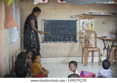 MUMBAI, INDIA - NOV 5: Unidentified children learn at a small classroom in the slum Dharavi on November 5, 2012 in Mumbai, India. Dharavi is the biggest slum in the world.  - stock photo