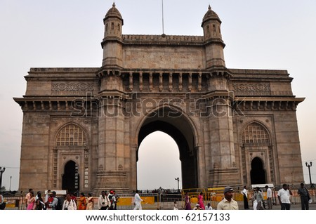 MUMBAI, INDIA - NOVEMBER 5: A group of people walk under the Gateway of India on November 5, 2009 in Mumbai. The Gateway was built to commemorate the visit of King George V and Queen Mary in 1911. - stock photo