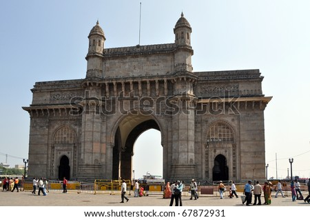 MUMBAI, INDIA - 5 NOVEMBER: A group of people walk under the Gateway of India on November 5, 2009. The Gateway was built to commemorate the visit of King George V and Queen Mary in 1911. - stock photo