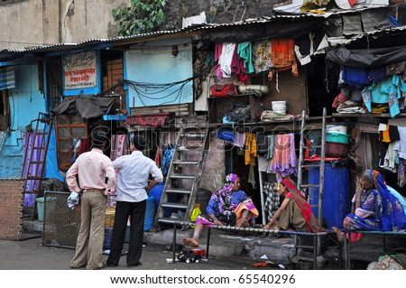 MUMBAI, INDIA - NOVEMBER 5: An unidentified Indian people sit on the street in the middle of slum on November 5, 2009. Slums are very common in every bigger city of India.