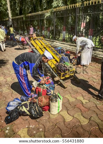 MUMBAI, INDIA - NOVEMBER 10, 2016: One dabbawala, or lunchbox delivery person, is transferring lunch bags and boxes to the cart of a second for delivery through the streets of Mumbai.