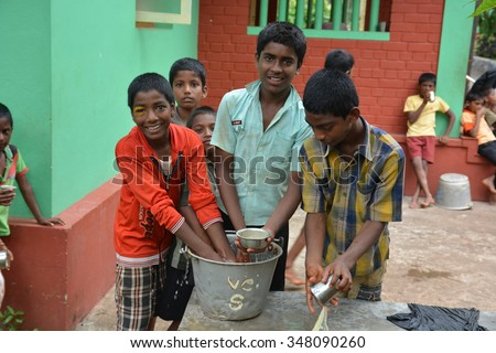 Mumbai, India - October 27, 2015 - Children from childrens home drinking water and washing dishes from new well powered by charity from europe