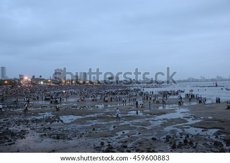 Mumbai, India - 14 SEPTEMBER 2015 - Crowds on the beach watching devotees pushing Hindu God Ganesha into the ocean