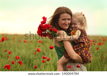 mummy with daughter at the poppies field   - stock photo
