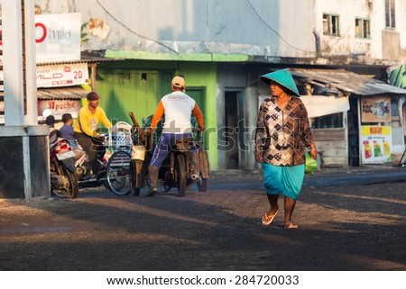 MUNCAR,JAVA,INDONESIA - May 24,2015 :Unidentified Indonesian women walks   in the street of traditional fishing village called Muncar,Indonesia.She wears traditional straw hat on her head.