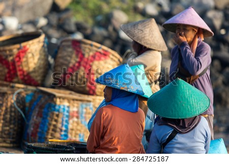 MUNCAR,JAVA,INDONESIA - May 24,2015 :Unidentified women,traditionally put straw hat on their head, stand and talk among them while they wait for the fishing boats so they will trade in fishing market
