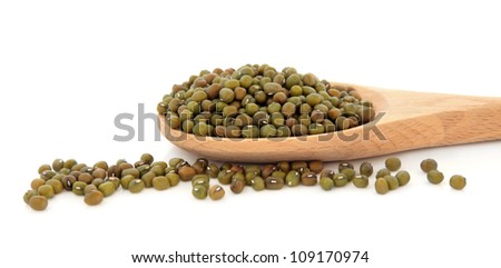 Mung bean pulses in a wooden cooking spoon over white background.