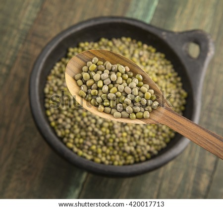 Mung beans in bowl and wooden spoon.