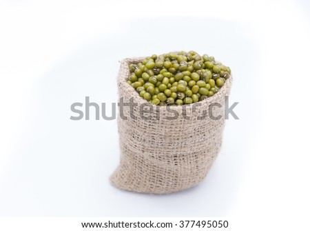 Mung beans over wooden spoon on white background - stock photo
