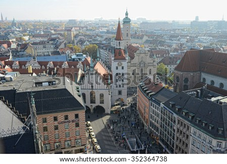 MUNICH, BAVARIA/ GERMANY October 28 2015: View over the Marienplatz from top of Town hall. In background old town hall and Heiliggeistkirche church. People walking across the place.