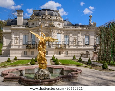 MUNICH (ETTAL, FUSSEN) GERMANY - 06 MAY 2016: Panoramic view to the fountain with sculpture of blowing gold angel, small green trees, walking alley and main building in the park of Linderhof Palace