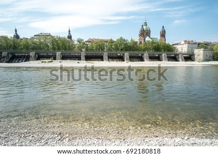 Munich, Germany - 21 April 2017 : View of building at the river bank of Isar river in Munich. WIth St Lukas Church on background.