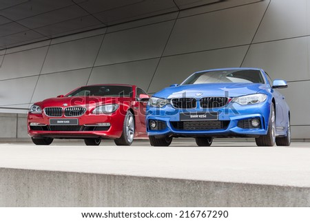 MUNICH, GERMANY - AUGUST 9, 2014: New modern models of executive business class BMW cars. Red 640i and blue 425d wet after rain autos. - stock photo
