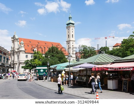 MUNICH, GERMANY - JULY 20: Tourists at the Viktualienmarkt in Munich,  Germamy on July 20, 2015. Munich is the biggest city of Bavaria with almost 100 million visitors a year.  - stock photo