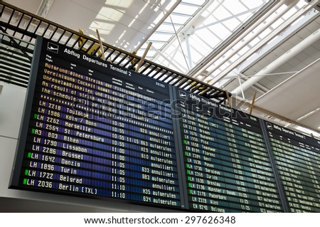 """Munich, Germany - March 20, 2015: Strike announcement on flight information board at Munich Airport: """"As result of strike actions of the pilots union the schedule will be reduced significantly.""""  - stock photo"""